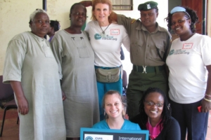 Rosemary Kombo with CCC staff, nurses, and patients pose proudly with International Medical Corps clinic sign.