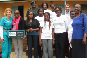CCC team and Langata Midwives pose happily after graduation with the International Medical Corps dedication sign.